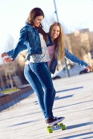 girl sport: Two Friends having fun with skate in the street Stock Photo