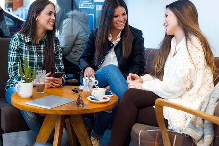adult student: Portrait of three young woman drinking coffee and speaking at cafe shop.