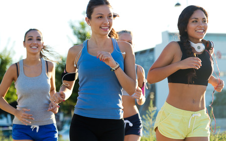 Outdoor portrait of group of women running in the park. Stockfoto