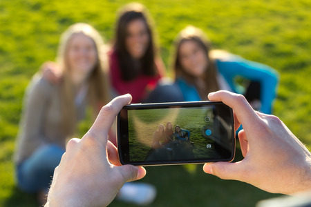 pictures: Outdoor portrait of group of friends taking photos with a smartphone in the park