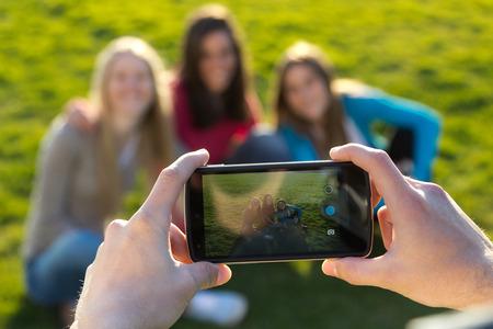 při pohledu na fotoaparát: Venkovní portrét skupinou přátel pořizování fotografií s smartphone v parku Reklamní fotografie