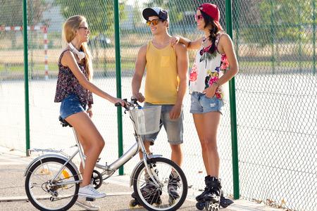 友人のグループが、ローラー スケートや自転車に乗って、公園での屋外のポートレート。