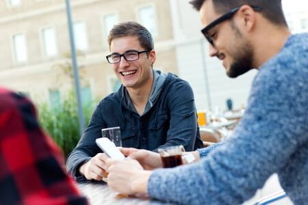 young entrepreneurs: Outdoor portrait of young entrepreneurs working at coffee bar. Stock Photo