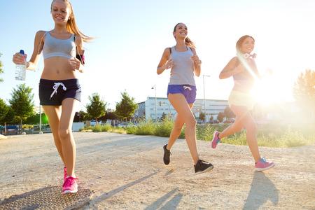 Outdoor portrait of group of women running in the park. Standard-Bild