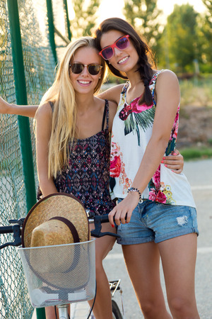 Outdoor portrait of young beautiful girls having fun in the park. Фото со стока