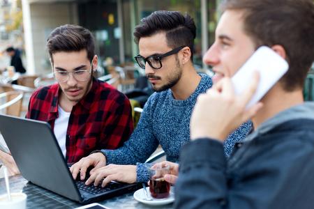 jovenes emprendedores: Retrato al aire libre de empresarios jóvenes que trabajan en el bar de café. Foto de archivo