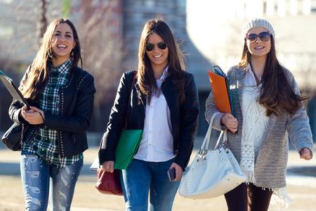 大学キャンパスにおける歩いている 3 人の学生の女の子の肖像画。