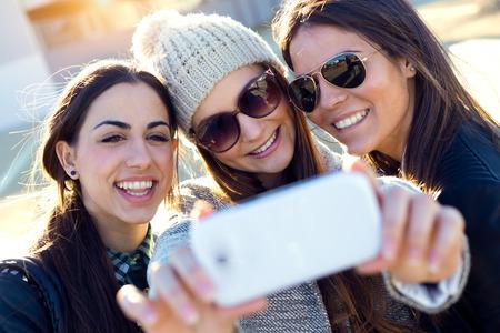 キャンパス内で携帯電話を使用して 3 つの学生の女の子の肖像画。