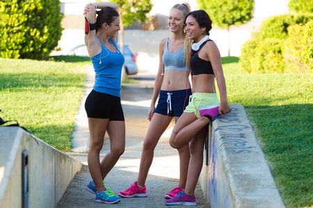 Outdoor portrait of group of young women doing stretching in the park. photo