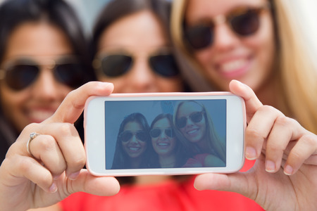 スマート フォンで写真を撮る 3 つの友人の肖像画