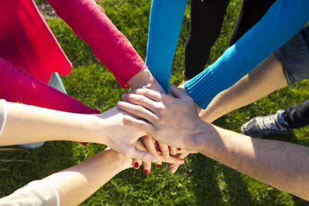Group of friends pile up hands as unity oath