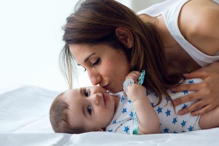 madre y bebe: Retrato de la madre y el bebé jugando y sonriendo en casa.