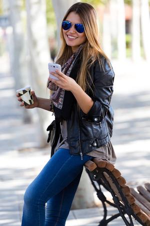 Outdoor portret van mooie meisje drinken koffie en met behulp van haar mobiele telefoon in de stad. Stockfoto