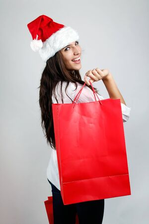 female christmas: Portrait of beautiful santa girl  carrying red shopping bags