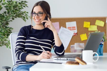 휴대 전화와 함께 그녀의 사무실에서 근무하는 확신 젊은 여자의 초상화입니다.