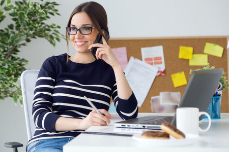 ouvrier: Portrait de confiance jeune femme travaillant dans son bureau avec un téléphone mobile.