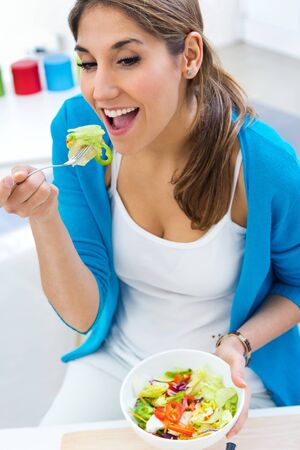 domiciles: Portrait of pretty young woman eating salad at home Stock Photo