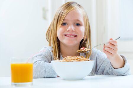comiendo cereal: Retrato de la hermosa niña de desayunar en casa.
