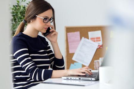 ノート パソコンと彼女のオフィスで働く自信を持って若い女性の肖像画。 写真素材