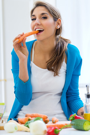 Portrait of pretty young woman having fun with a carrot in the kitchen
