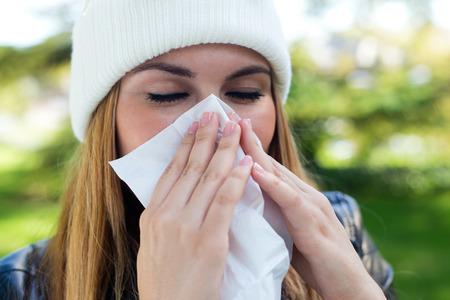 enfermos: Retrato al aire libre de la muchacha hermosa con el tejido que tiene gripe o alergia. Foto de archivo