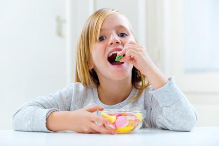 家でお菓子を食べる美しい子供の肖像画。