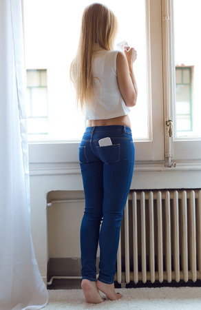 Portrait of young beautiful woman at home with mobile phone in back pocket.
