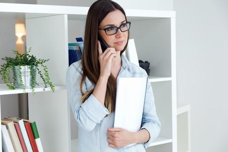 携帯電話で彼女のオフィスで働く自信を持って若い女性の肖像画。