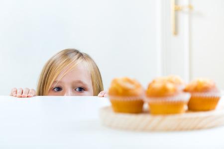 Portret van mooi kind thuis ontbijten.