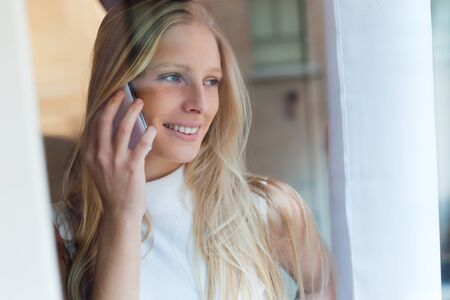 Portrait of young beautiful woman using her mobile phone at home. photo