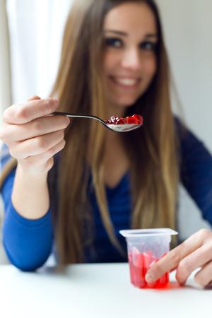 Portret van jonge mooie vrouw die yoghurt eet thuis. Stockfoto