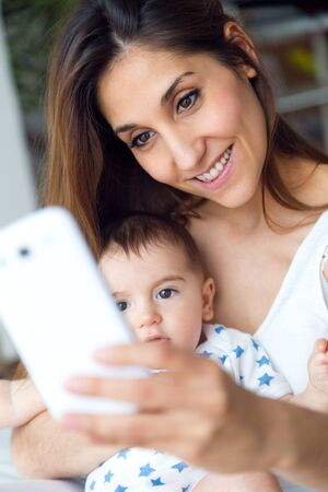 the caucasian beauty: Portrait of beautiful mother and baby taking a selfie at home.