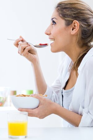 woman eating: Portrait of young pretty woman eating cereals in the morning