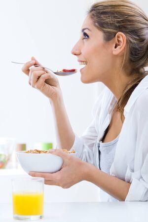 comiendo cereal: Retrato de mujer joven comer cereales bonito por la mañana Foto de archivo