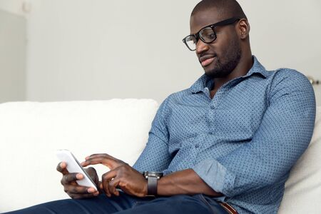 man on cell phone: Portrait of handsome young man using his mobile phone at home. Stock Photo