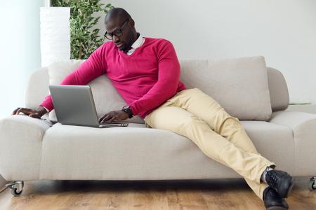 hombres negros: Retrato de hombre joven hermoso que trabaja con su computadora port�til en casa. Foto de archivo