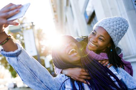 Portret van mooie jonge vrouw twee die mobiele telefoon in de straat met behulp van. Stockfoto