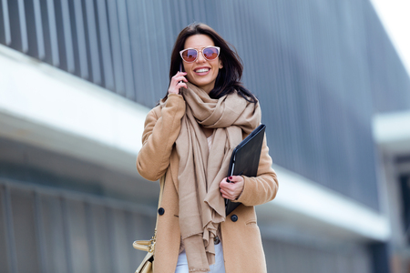 Portrait of beautiful young woman using her mobile phone in the street. Stock Photo