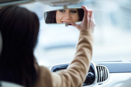Portrait of beautiful young woman fixing rear view mirror of the car.