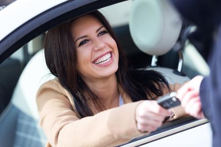 Retrato do empregado da agência do aluguer de carros que dá chaves do carro à jovem mulher bonita.