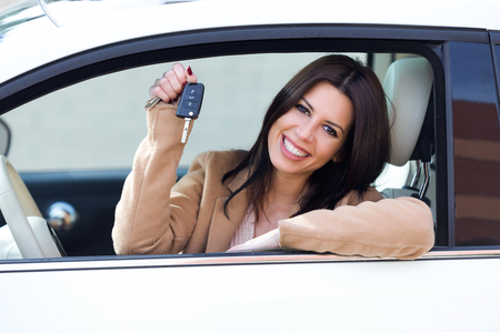 Portrait of beautiful young woman driver holding auto keys in her new car.