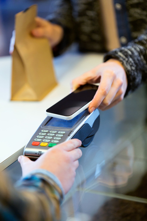 Portrait of customer using her smartphone to make mobile payment with electronic reader. Stock Photo