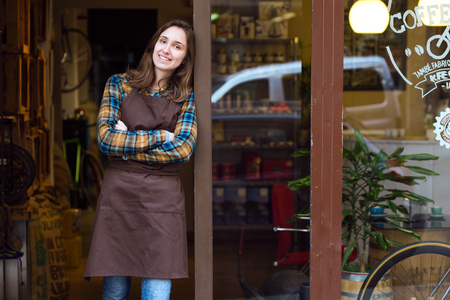Portrait of beautiful young saleswoman looking at camera and leaning against the door frame of an organic store.
