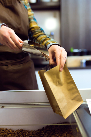Close-up of a saleswoman selling bulk coffee at an organic store.