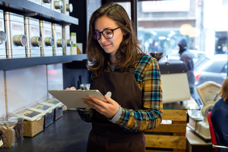 Portrait of beautiful young saleswoman doing inventory in a retail store selling coffee. Stock Photo
