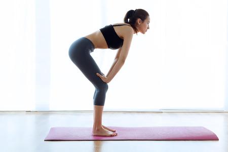 Retrato de mujer joven deportiva haciendo abdominales hipopresivos interior.
