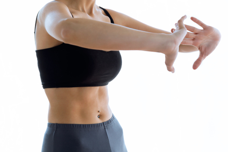 Close-up of sporty young woman doing hypopressive abs indoor. Stock Photo