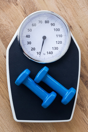 Close up of blue dumbbells on top of weight scale on wooden background in the gym.