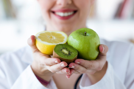Close-up of doctor hands holding fruit such as apple, kiwi and lemon. Zdjęcie Seryjne