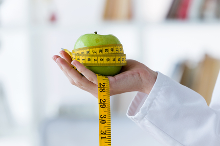 Close up of female hand holding a green apple wrapped in a tape measure.